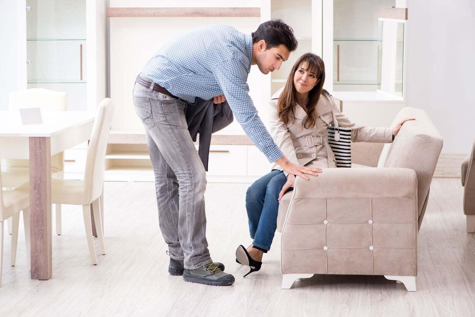 A man and a woman in a store looking at a sofa.