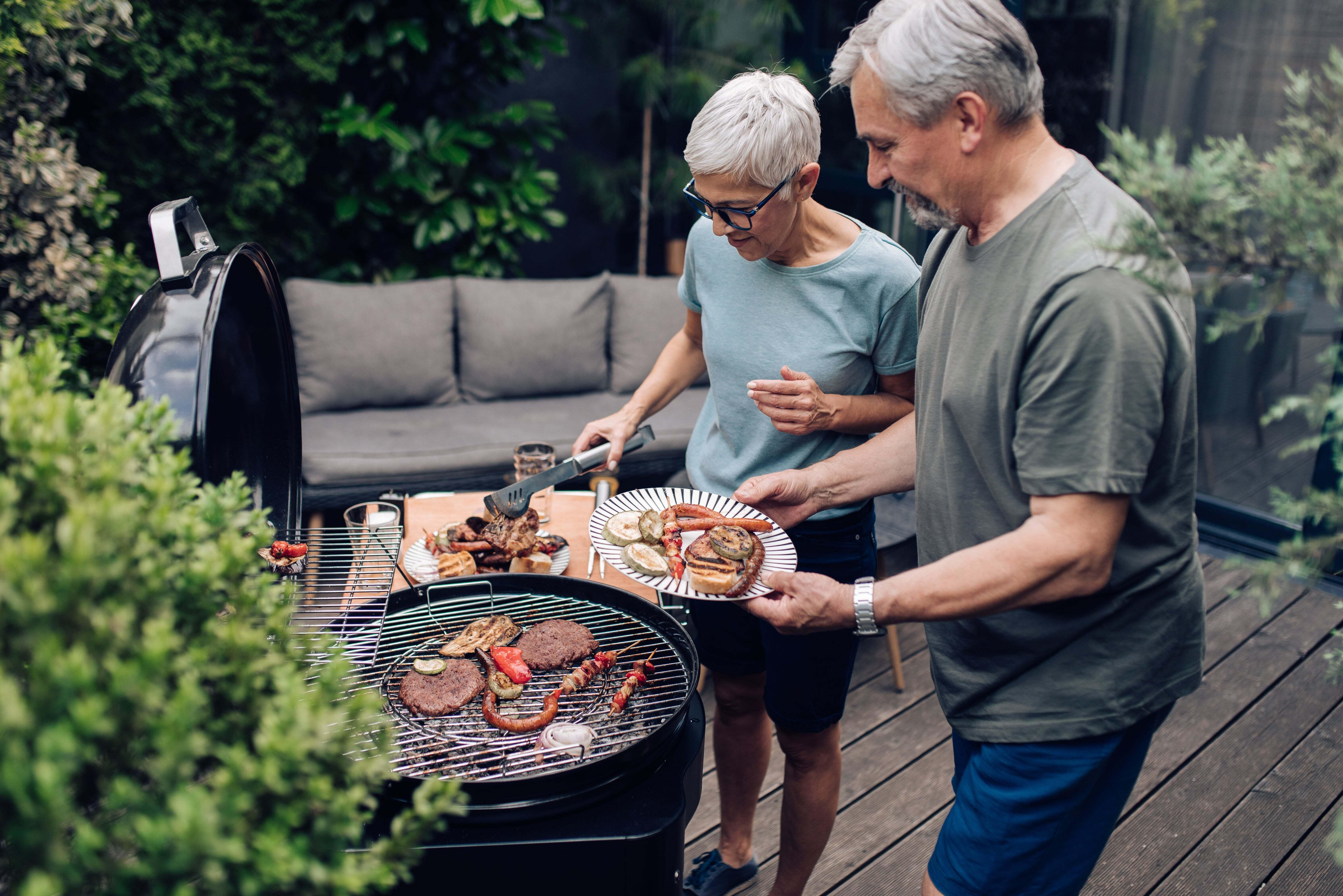 An older couple grilling on their patio outdoors