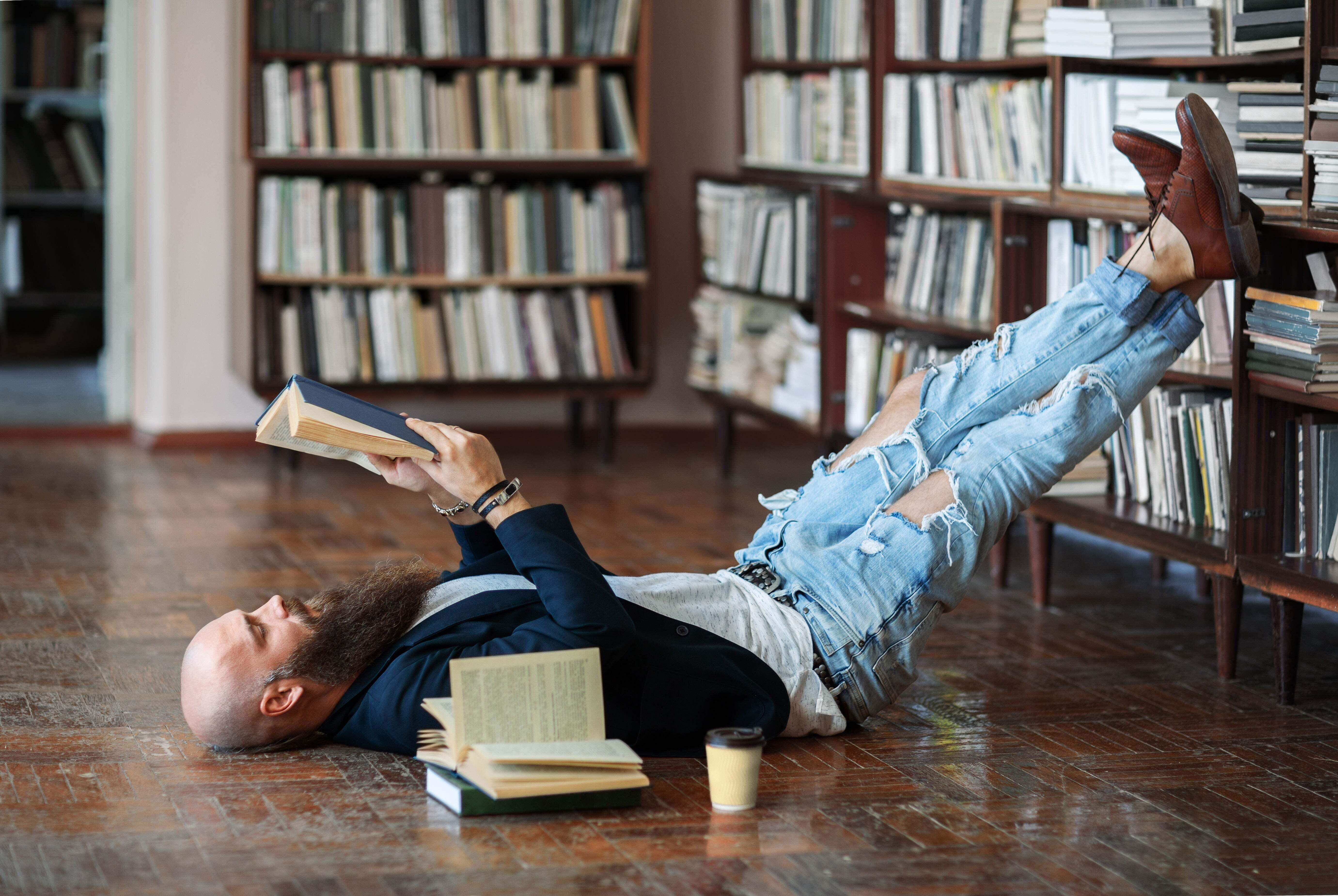 A man reading a book while propping his feet on a bookshelf