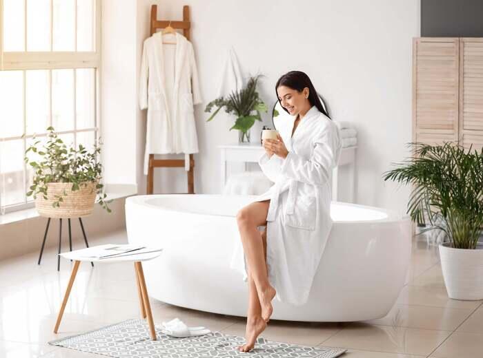 A woman sitting on the edge of a bathtub