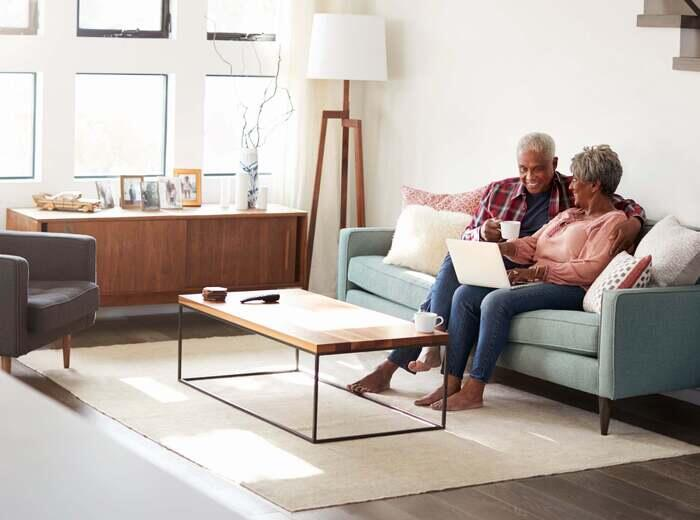 A couple sitting on a sofa with an area rug below their feet