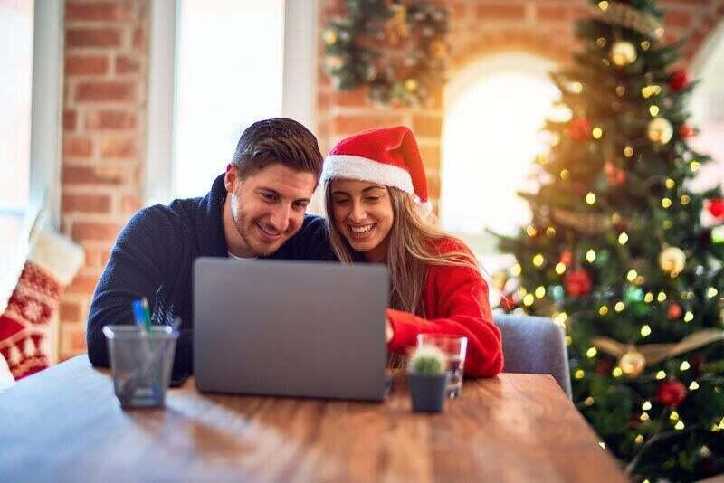 A couple is watching a laptop while sitting in a holiday festive room.
