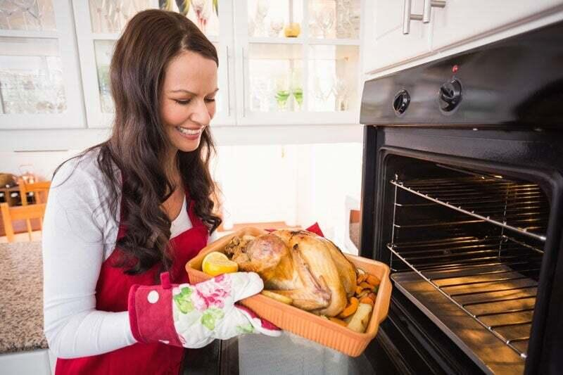 A woman is placing a turkey into the range in her kitchen.