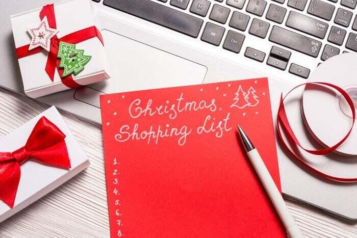 A holiday shopping list is laid out on a desk.