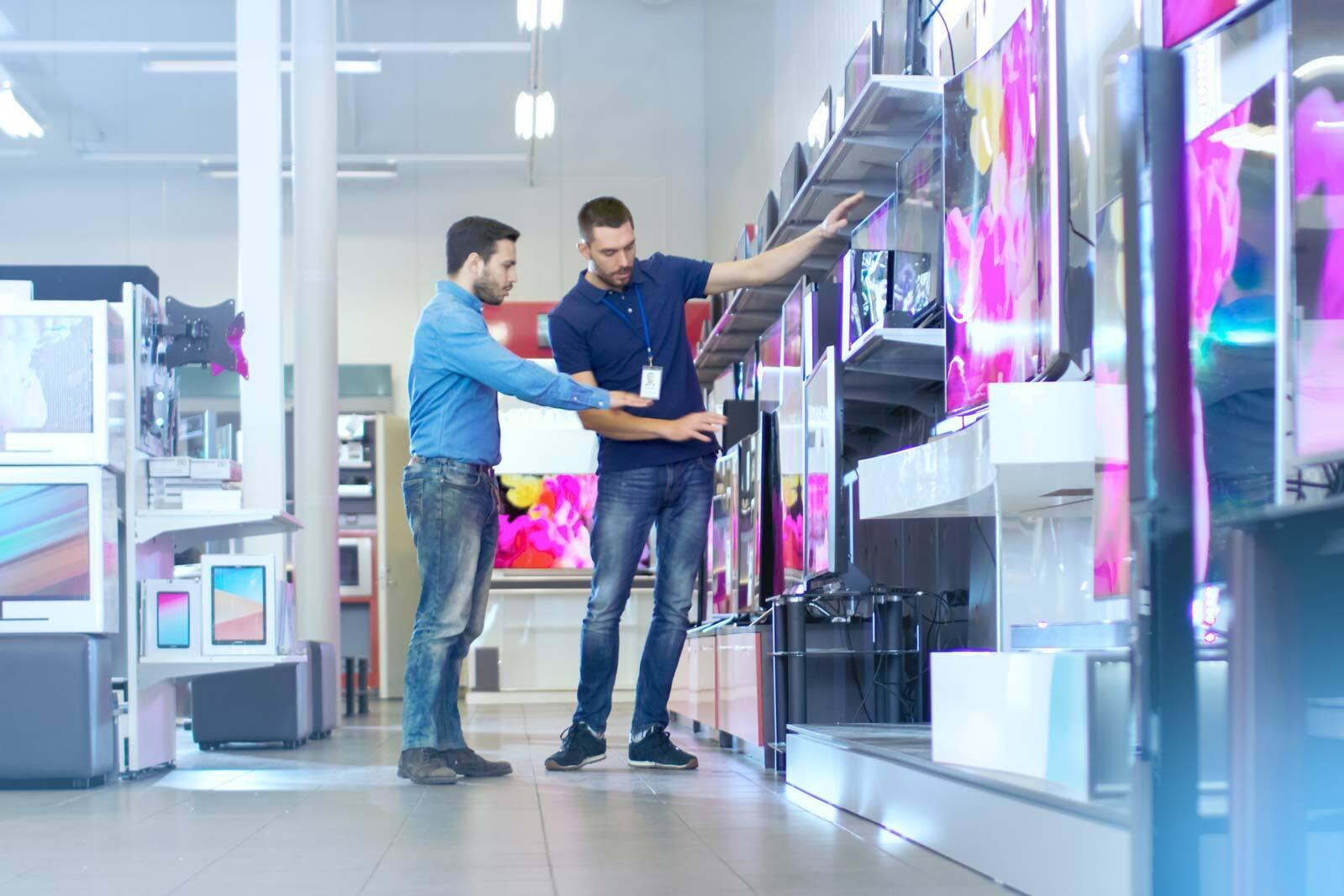 A man is shopping for TVs in a store and is talking to a salesperson.
