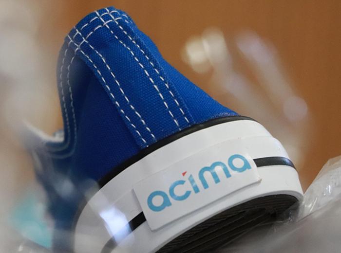 A blue shoe showing the Acima logo