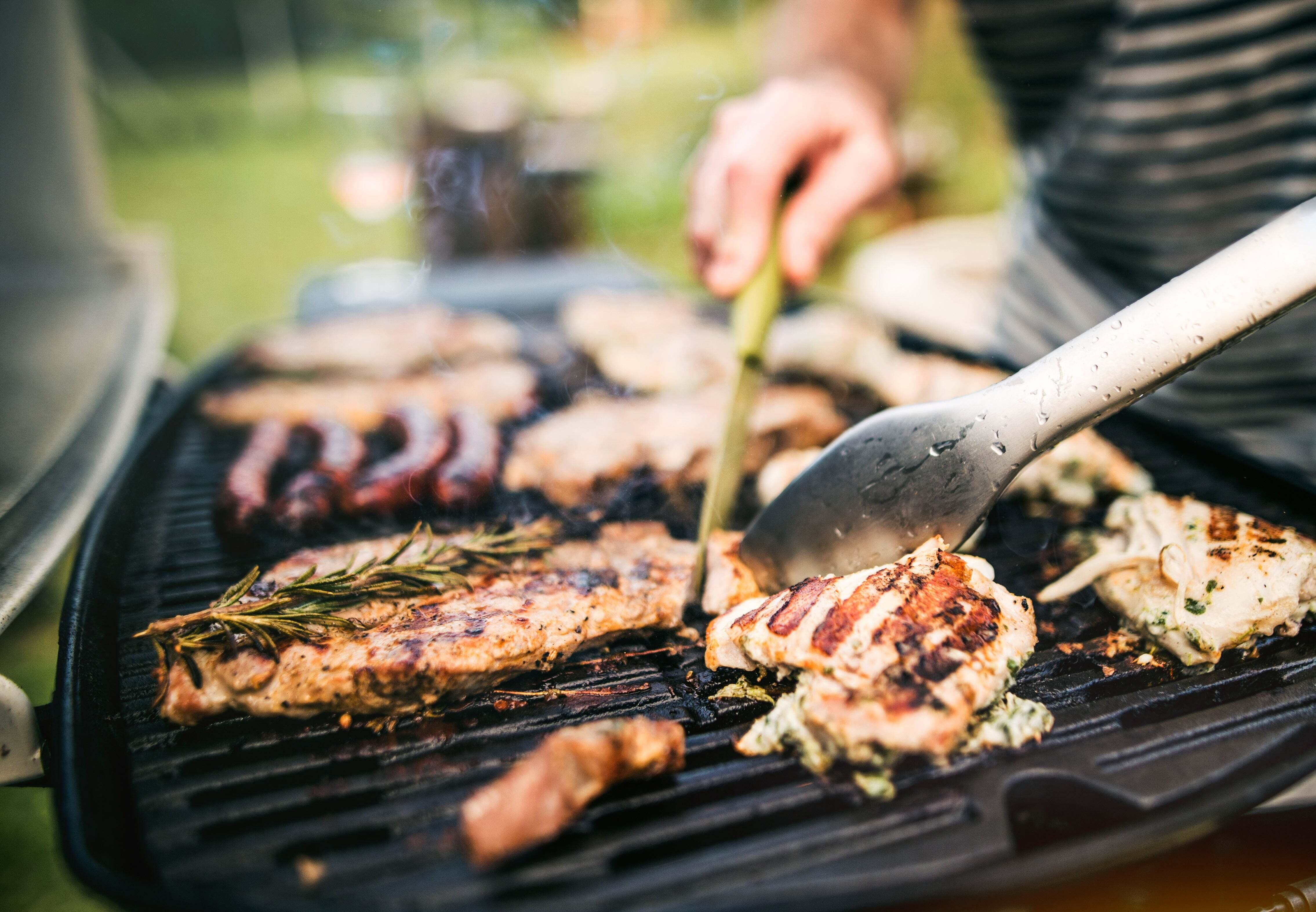 A man grilling chicken on an electric grill