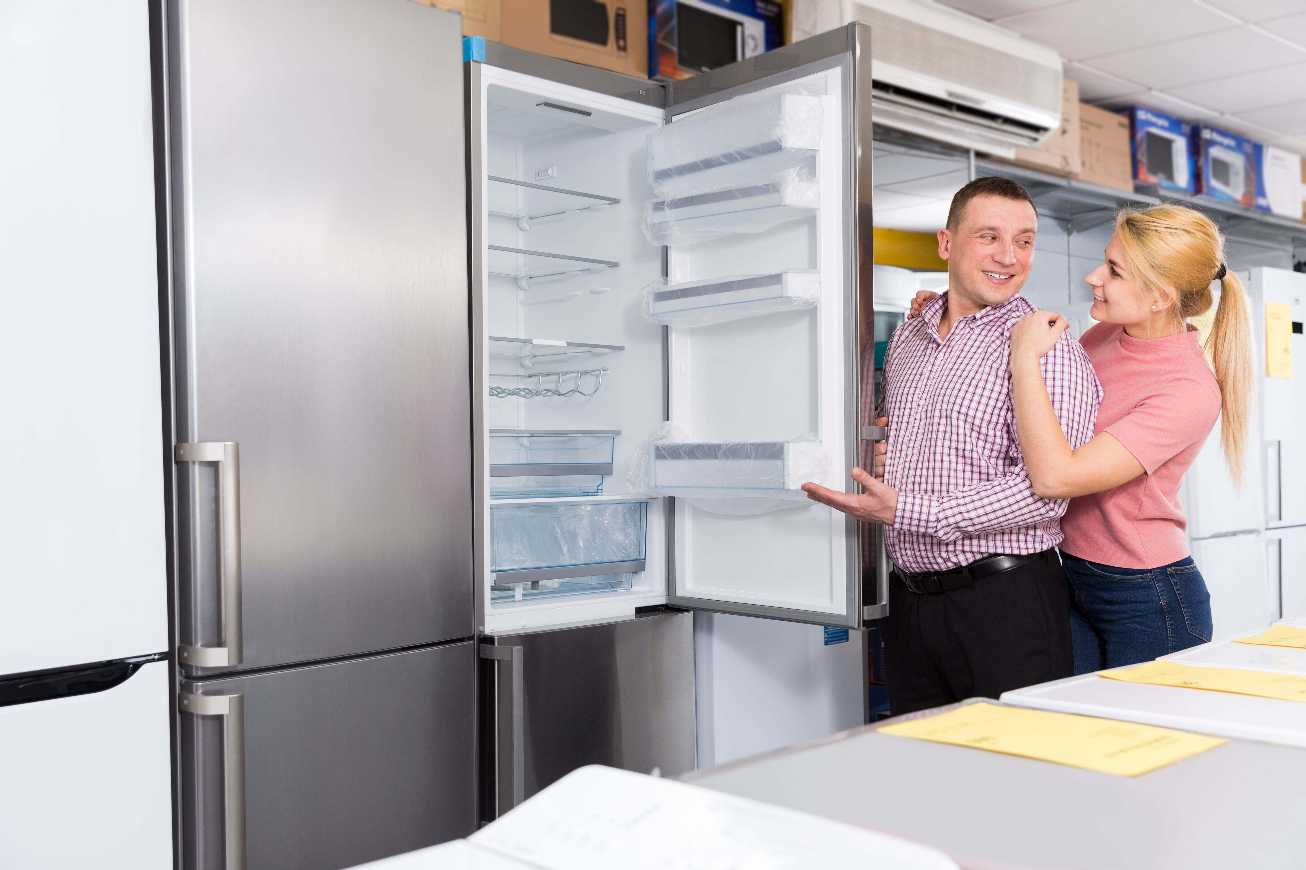 A couple looking at a fridge in a store