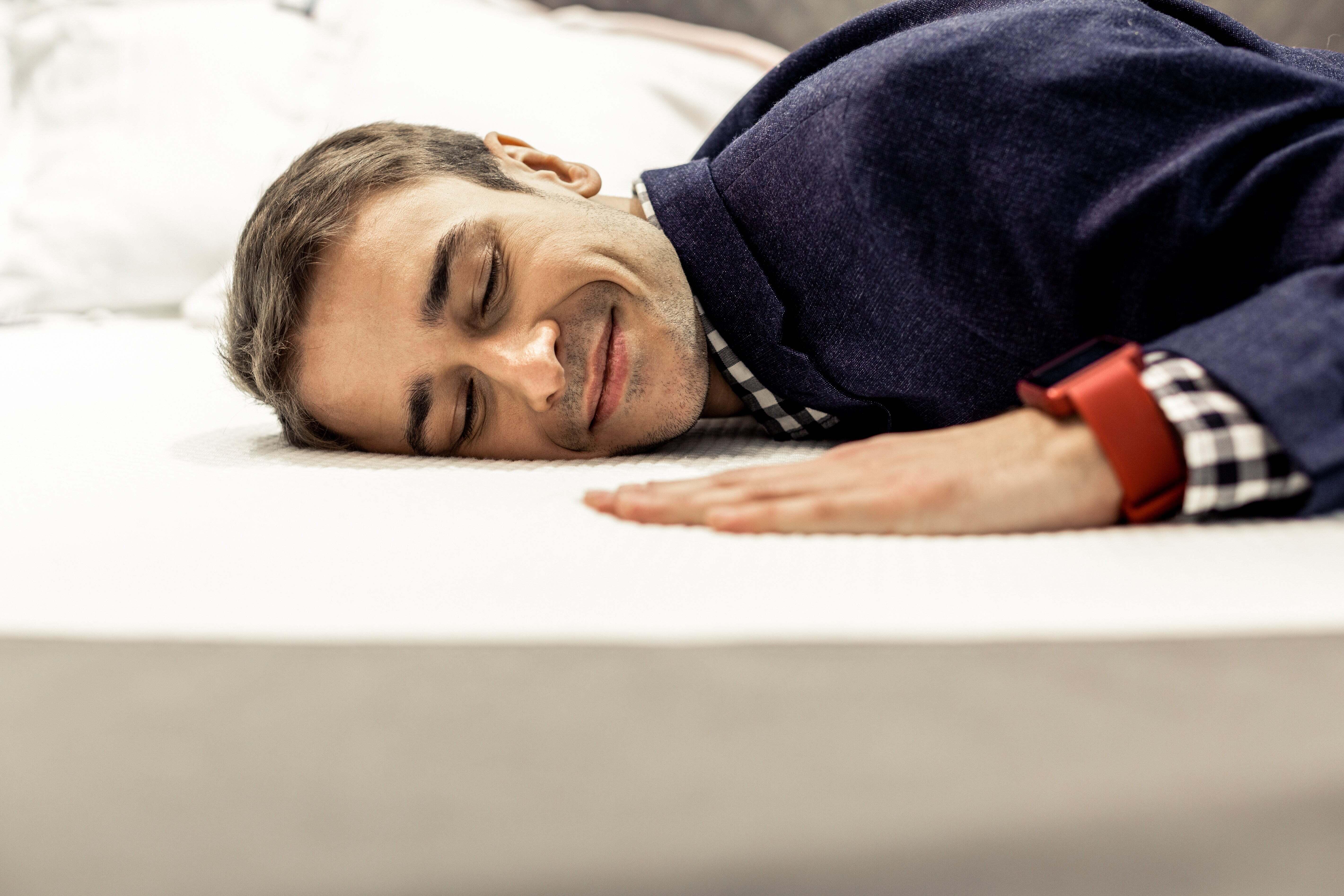 A man laying on a mattress smiling
