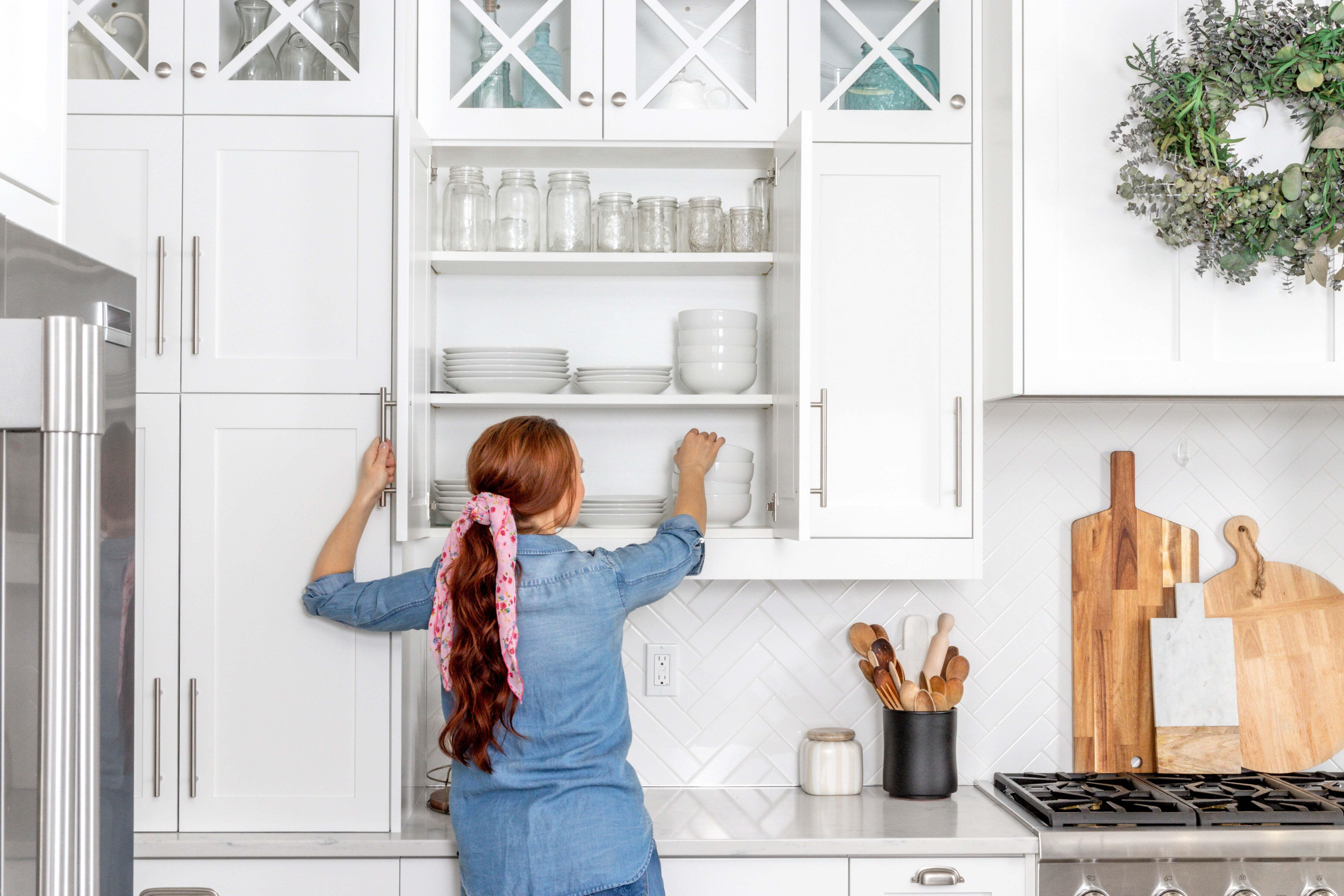 A woman is taking out a bowl from her kitchen cabinets.