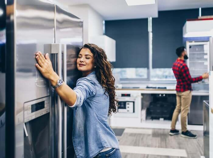 A woman hugging a refrigerator