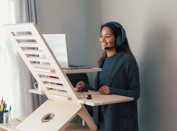 A woman smiling while working at a standing desk