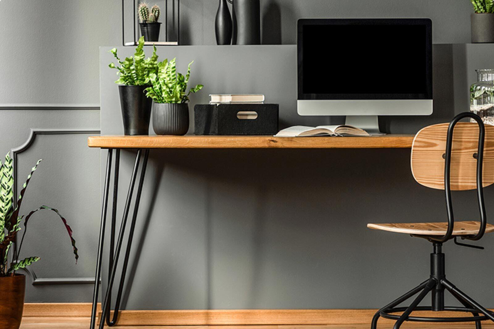A comfortable desk set-up with a desktop computer is against a wall.