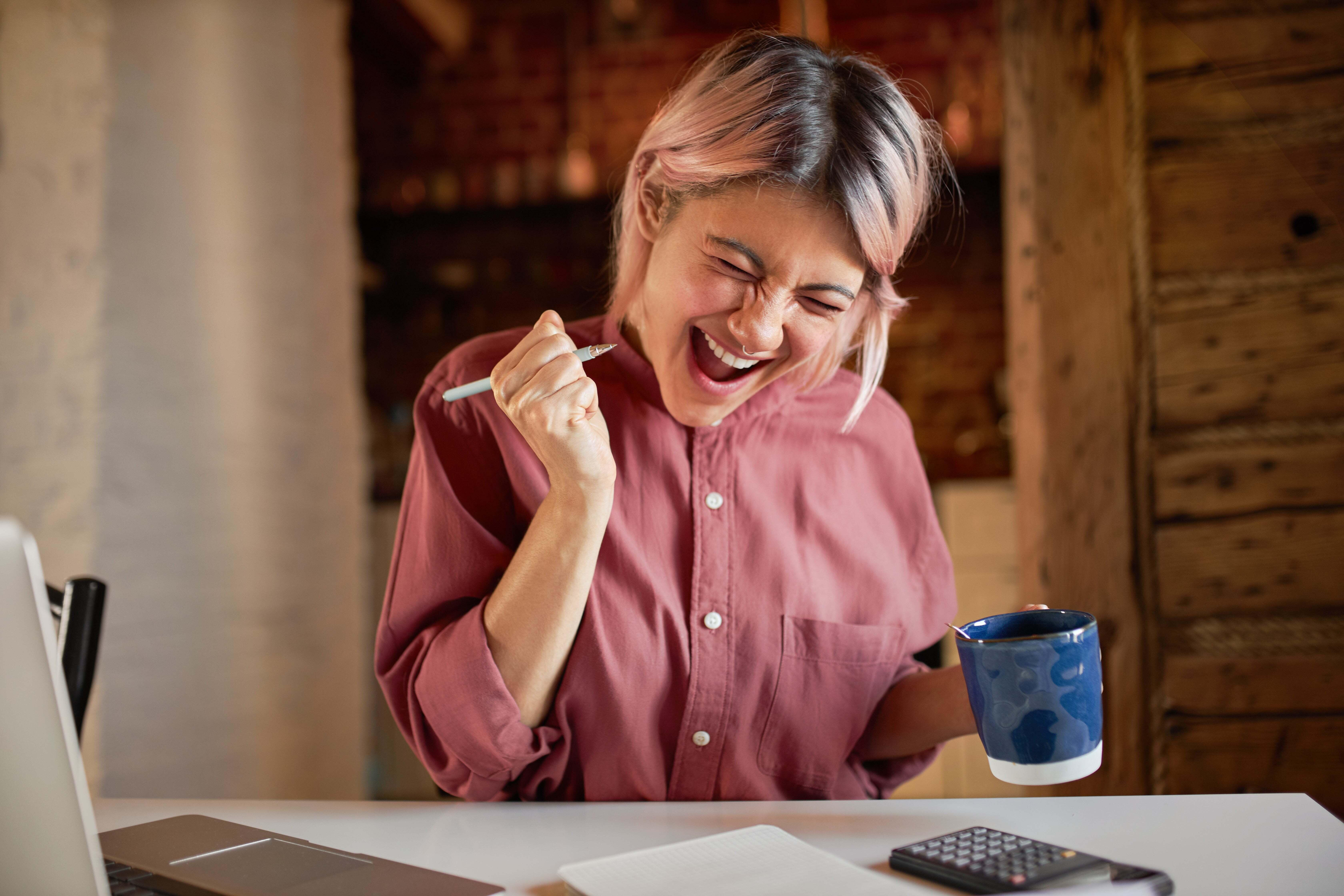 A woman cheering as she looks at her spreadsheet.