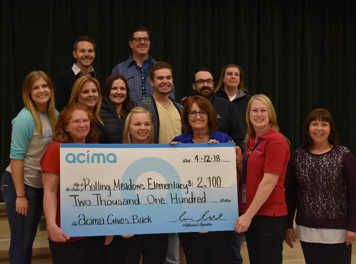 A group of teachers holding a large paper check